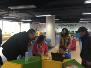 Tai and Charles watch child use laptop at Library for the Blind