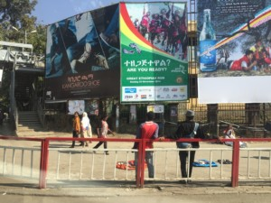 People walking under huge advertisements in downtown Addis.