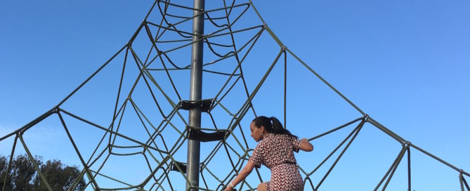 Haben climbs a large pyramid-shaped jungle gym that has multiple routes to the top. She is about two thirds of the way up the 20-foot high rope structure. Trees and blue skies are in the background.