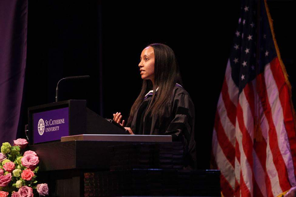 Haben is standing at the St. Catherine University podium wearing academic regalia, and behind her is a US flag.