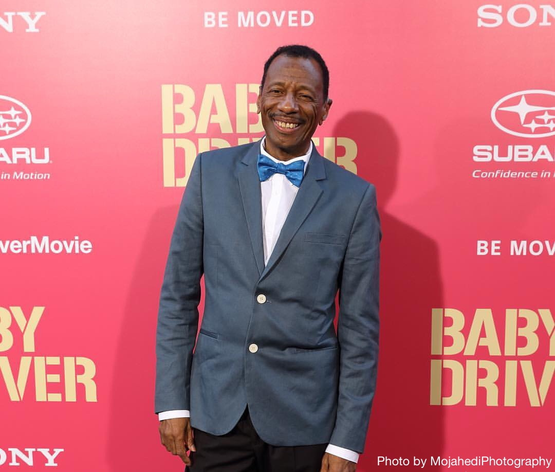 Actor CJ Jones standing in front of a pink poster for the movie Baby Driver. Photo by MojahediPhotography