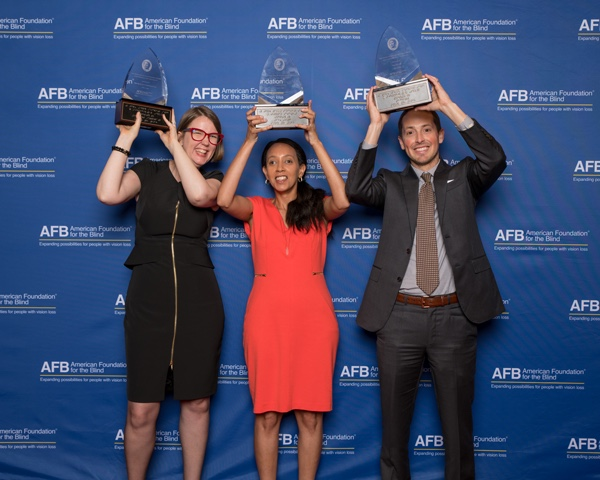 Jenny Lay-Flurrie, Haben Girma, and Jeff Wieland are each holding up a Helen Keller Achievement Award in front of a blue backdrop that says AFB American Foundation for the Blind. Photo by AFB.