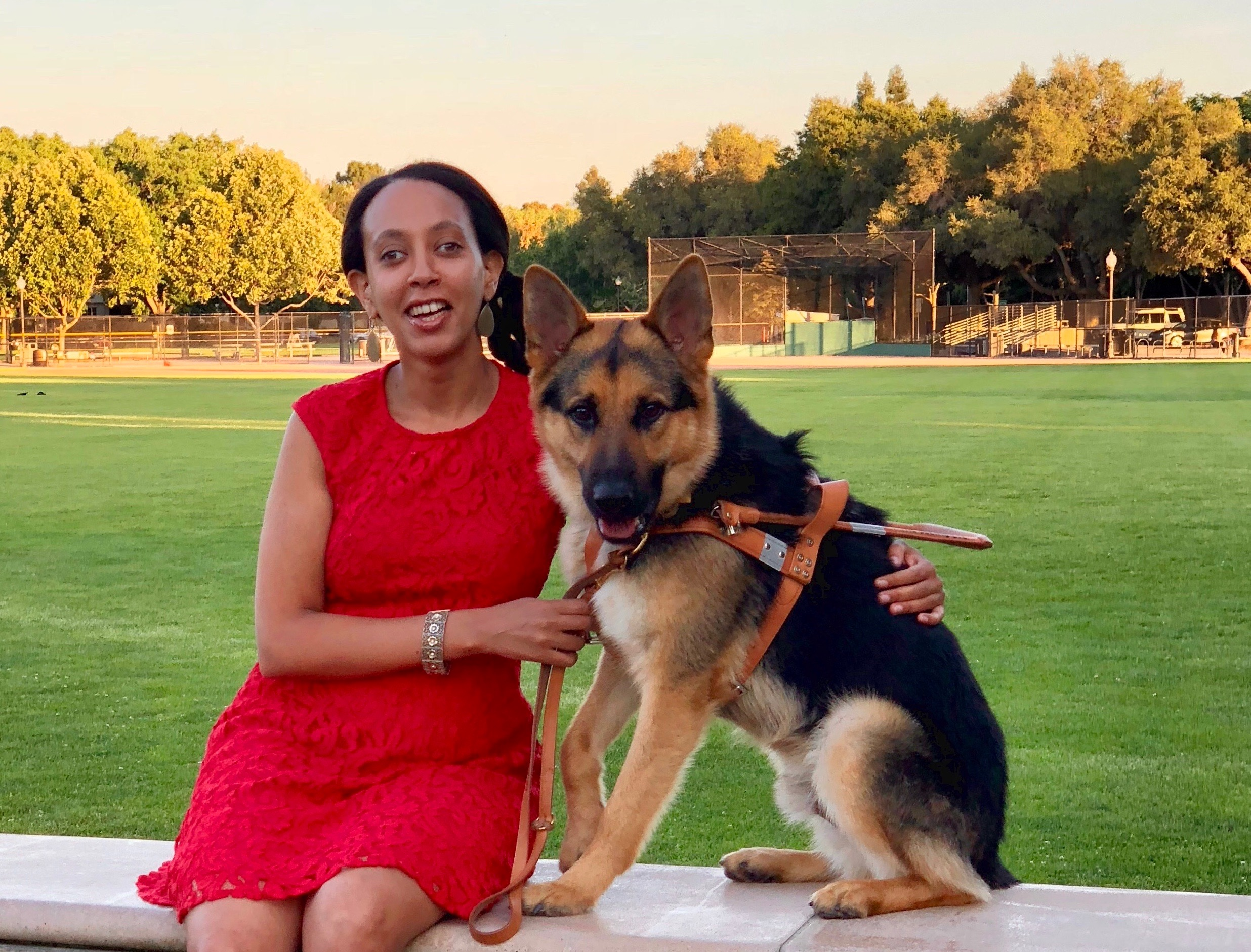 Haben and Mylo are sitting on a bench. Mylo is a black and tan medium-sized German Shepherd dog. He's wearing a leather harness, and Haben is holding his leash. Behind them is a large grassy field with trees in the distance