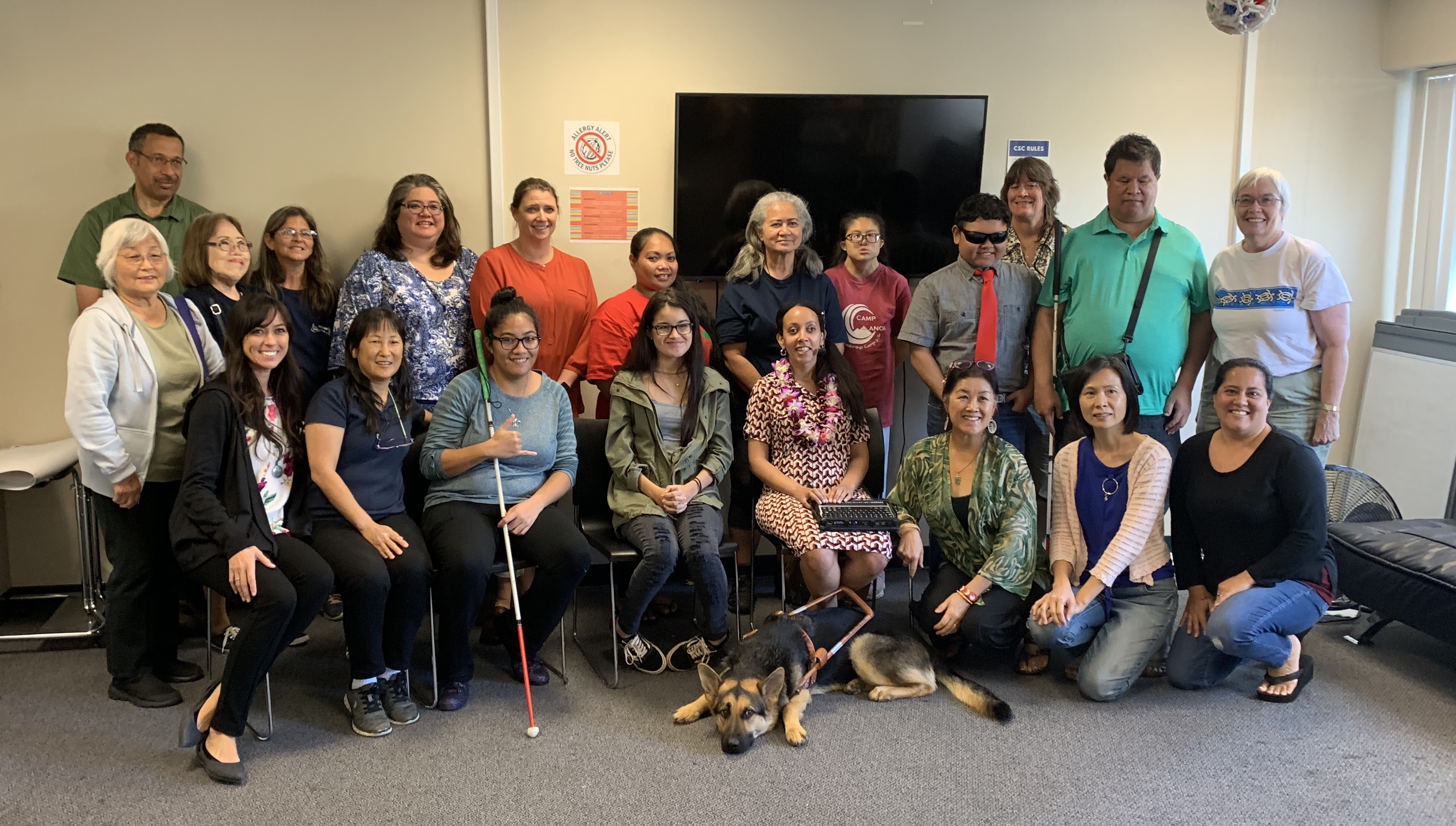 Twenty members of the Hawaii Deafblind community, from high school students to grandparents, stand together. Haben is wearing two leis gifted to her by the kupuna, the elders. One has smooth kukui nuts, the other has orchids, carnations, and tuberoses that smell AMAZING! Mylo, Haben's Seeing Eye dog, is stretched out on the floor in front of Haben