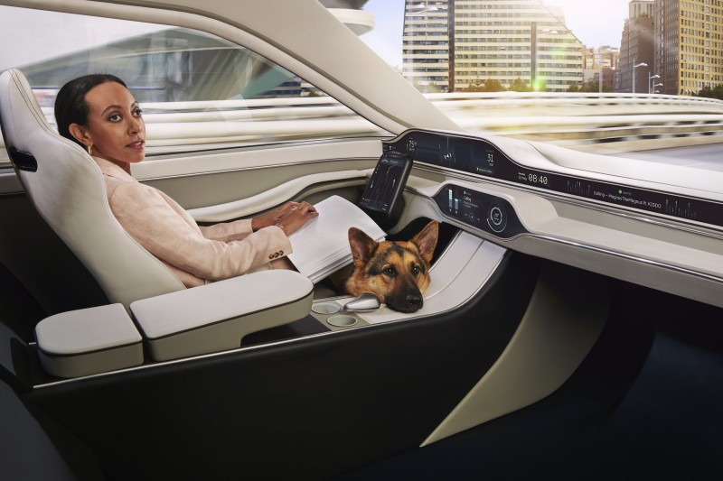 Haben is casually reading a page of braille in the driver's seat of a car. The driver's seat doesn't have a steering wheel, just a touchscreen tablet. In the film Haben controls the tablet with her braille computer. An adorable German Shepherd dog is on the floor, his head peaking up over the central panel.