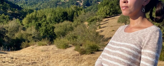 I'm standing on a ridge overlooking the green and yellow hills of Portola Valley. My arms are crossed, and Mylo's leash is looped through an arm.
