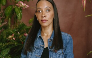 I, Haben, a Black woman with long black hair, am sitting on a stool in front of a brown background and green leaves with pink floral arrangements. I'm wearing a denim jacket over a black top and white patterned skirt