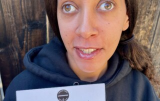 I'm wearing a black hoodie with the book club's name Underrated on the left side. I'm smiling and holding up the card. A dark brown fence is in the background.
