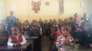 Young children sitting at their desks at the Victory School for the Deaf.