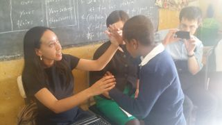 Haben tactile signing with student Kadus at the Victory School for the Deaf.