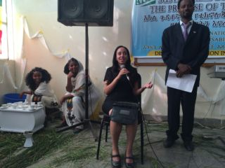 Haben sitting and speaking into microphone at Mekelle university event.