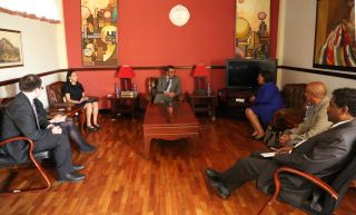 Dr. Tedros, Haben, and Haben's team seated in an office.
